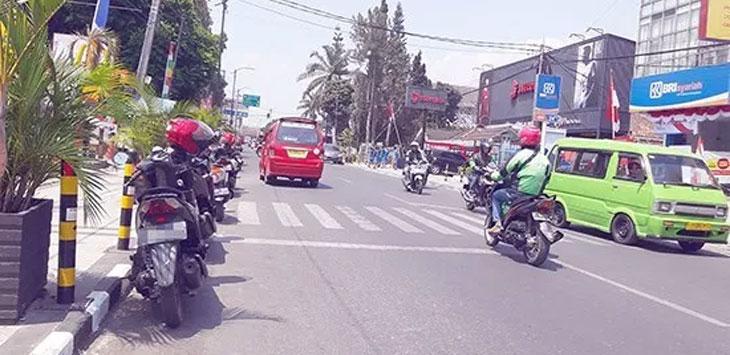 Pemandangan kendaraan yang memarkir kendaraannya di zona larangan parkir.