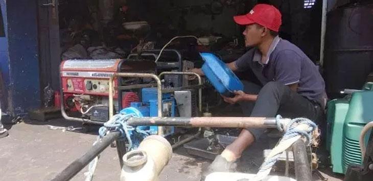 Agus Ridwan (42), salah seorang karyawan bengkel service genset Berkah Jaya Motor yang berlokasi di Jalan RA Kosasih yang kebanjiran order.