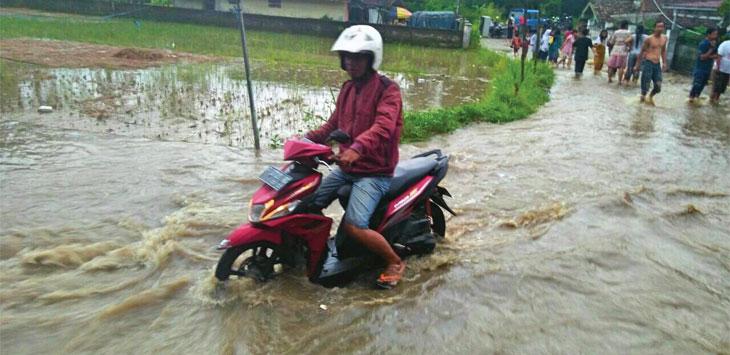 Seorang pengendara motor saat melintasi jalan yang digenangi air genangan.