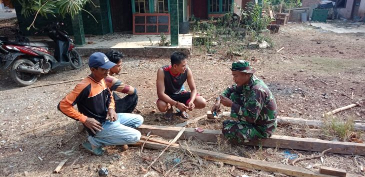 Salah seorang anggota TNI dari Kodim 0619 Purwakarta, saat melakukan kunjungan ke warga yang sedang gotong royong sekaligus persiapan jelang TMMD di Desa Cisaat Campaka.