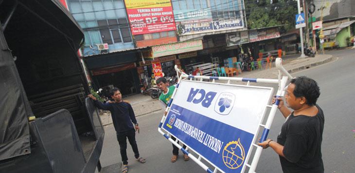 Pekerja mengangkut pembatas jalan di kawasan Jalan Arif Rahman Hakim, Minggu (8/9). Jalan tersebut kembali diberlakukan Sistem Satu Arah (SSA). Radar Depok