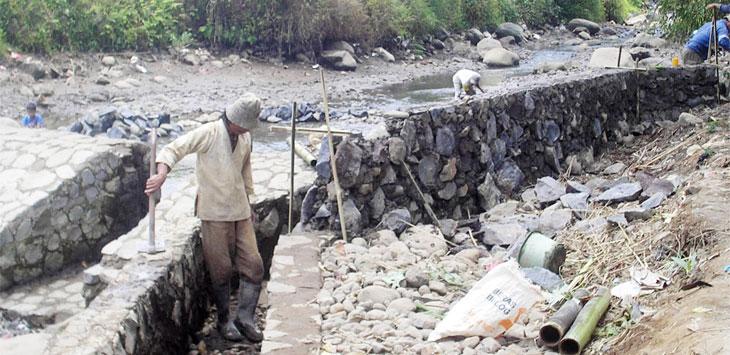 Sejumlah warga bergotong-royong memperbaiki saluran irigasi yang rusak.