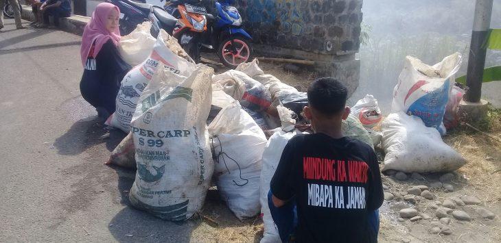 Sepasang remaja anggota Gema Sunda sedang mengumpulkan sampah-sampah dari sungai ciherang pondoksalam.
