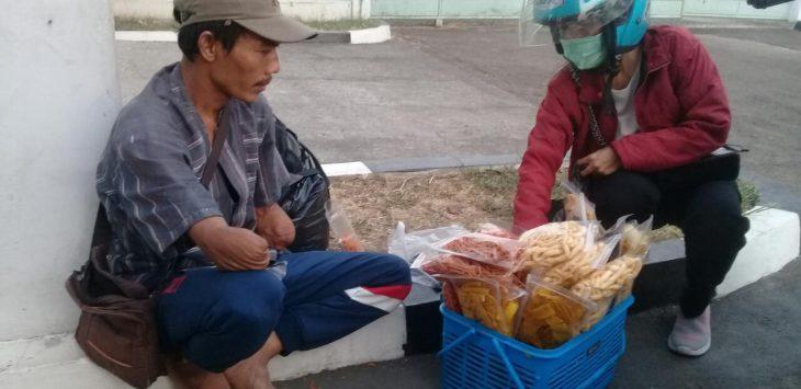 Yana (43) pria tuna daksa, saat melayani pembeli yang hendak membeli barang makanan ringan miliknya di sudut spbu jalan veteran purwakarta.