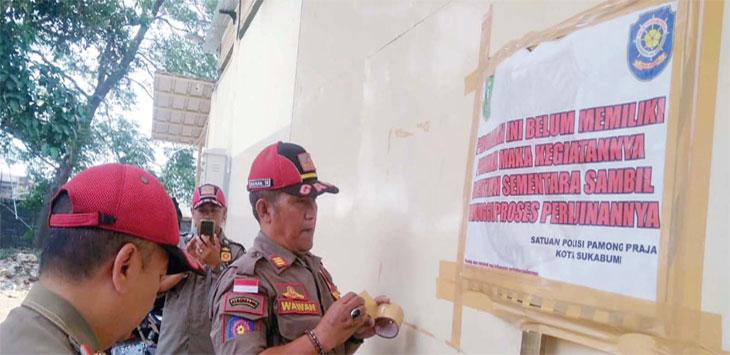 Satpol PP Kota Sukabumi saat menyegel gudang milik PT Yomart Rukun Selalu yang berlokasi di Jalan Pelabuhan II, RT 4/13 Kelurahan Dayeuhluhur Kecamatan Warudoyong.