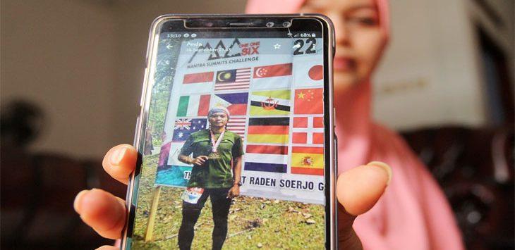 Indriyani (32) menunjukkan foto adiknya Dede Saifulloh (27) yang kini menjalani perawatan intensif usai terjatuh saat mengikuti Race Sarawak Adventure Challenge, Malaysia di kediamannya Jalan Bambon III, RT3/RW1, No.78A, Kelurahan Beji Timur, Kecamatan Beji, Selasa (16/10/19). Radar Depok
