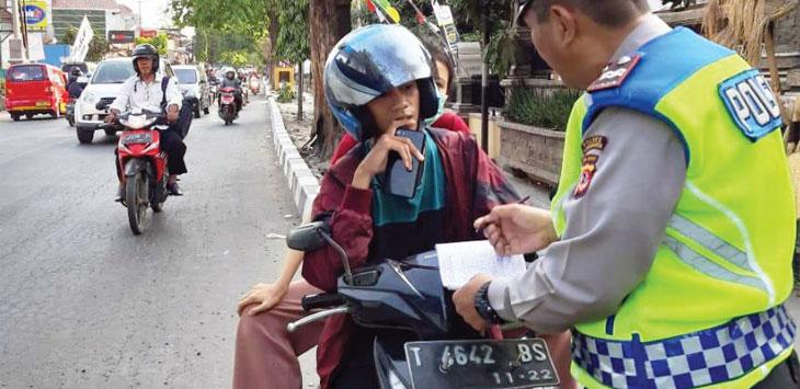 Pengendara sepeda motor saat diperiksa kelengkapan surat-suratnya.