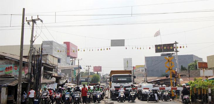 Sejumlah kendaraan terjebak kemacetan saat menunggu kereta melintas di pintu perlintasan Jalan Dewi Sartika, Kecamatan Pancoranmas. Radar Depok