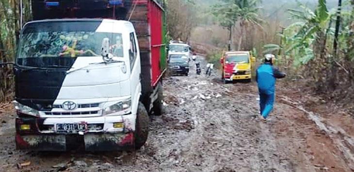 Sejumlah truk nampak berhati-hati saat melintasi jalan poros Kecamatan Pabuaran karena kondisi jalan yang rusak parah.