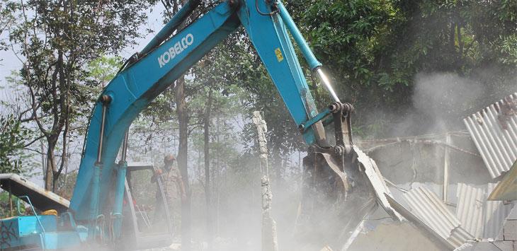 Petugas menggunakan alat berat untuk merobohkan bangunan di lahan yang akan dijadikan Universitas Islam Internasional Indonesia (UIII) di kawasan Kelurahan Cisalak, Kecamatan Sukmajaya, Rabu (13/11/19). Radar Depok