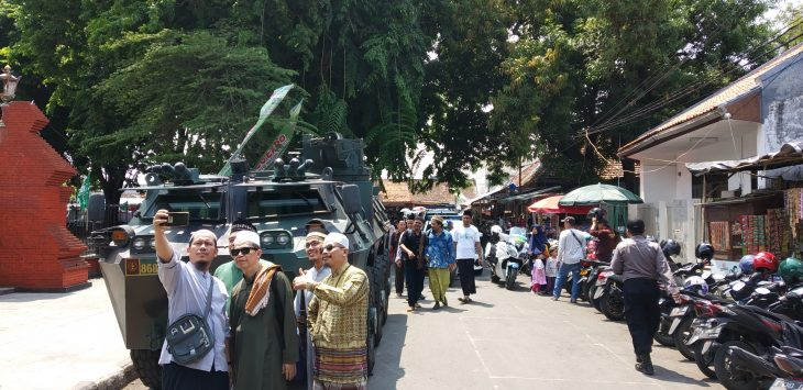 Warga bersuafoto di depan kendaraan tempur milik TNI. Dede