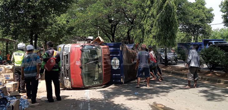 Truk bermuatan air mineral dievakuasi petugas Unit Lantas Polrestro Depok dibantu warga, setelah terguling di ruas Jalan Raya Juanda, Senin (18/11/19) pukul 10.30 wib. Radar Depok