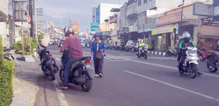 Salah seorang juru parkir di Jalan Sudirman Kota Sukabumi saat menjalankan aktivitas kesehariannya.