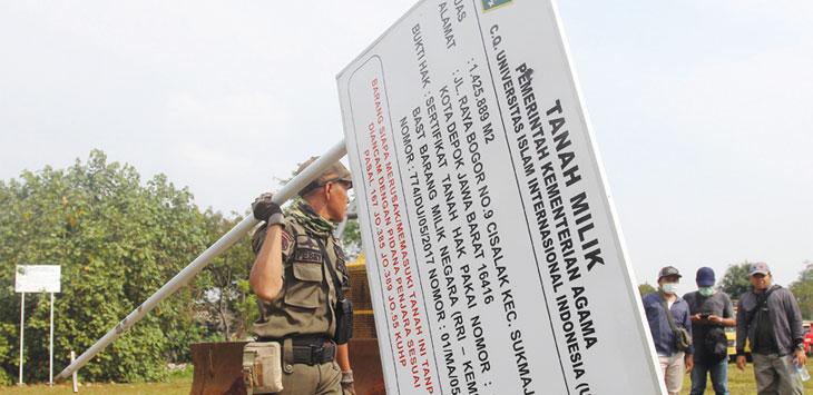 Petugas membawa bukti kepemilikan tanah UIII di kawasan Kelurahan Cisalak, Kecamatan Sukmajaya, Rabu (13/11/19). Radar Depok