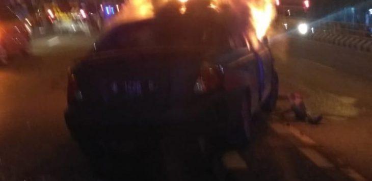 Mobil perampok terbakar setelah menabrak PJU. ist