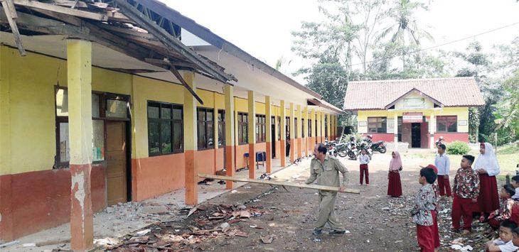 Ketua Komite SDN Sangkalih, Engkos Kosasih bersama para guru saat membersihkan material bangunan kelas dua yang ambruk, rabu (4/12/19).