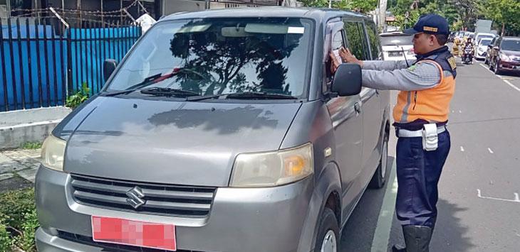 Salah seorang petugas Dishub Kota Sukabumi menempelkan stiker peringatan kepada mobil berplat merah yang melakukan parkir pada zona larangan parkir.