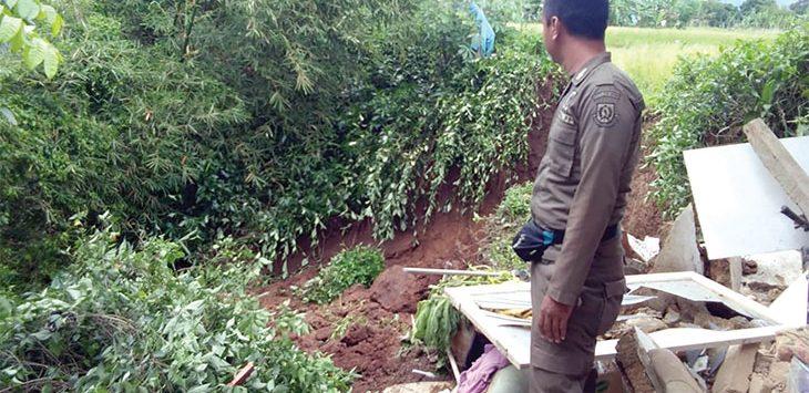 Salah seorang petugas Satpol PP saat meninjau lokasi longsor.
