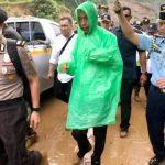 Presiden Jokowi mengenakan jas hujan saat diguyur hujan di Desa Harkat Jaya Sukajaya (ist)