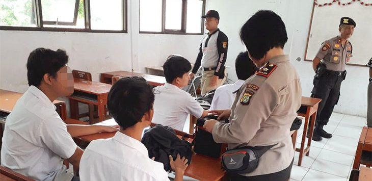 Sejumlah petugas kepolisian memeriksa tas pelajar disebuah sekolah, yang diduga turut dalam aksi tawuran pelajar.