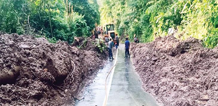 Petugas gabungan saat membersihkan material longsoran yang menimbun Jalan Raya Propinsi Jawa Barat, tepatnya di jalan Cipecang sampai jalan Batu Cakup, Kecamatan Ciemas.
