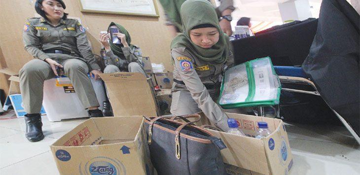 Petugas Satpol PP Kota Depok mendata barang yang disita dari peserta Calon Pegawai Negeri Sipil (CPNS) di Hotel Bumi Wiyata, Jumat (14/2/2020). Radar Depok