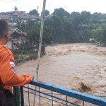 Salah seorang petugas BPBD tengah memantau langsung aliran air Sungai Ciliwung