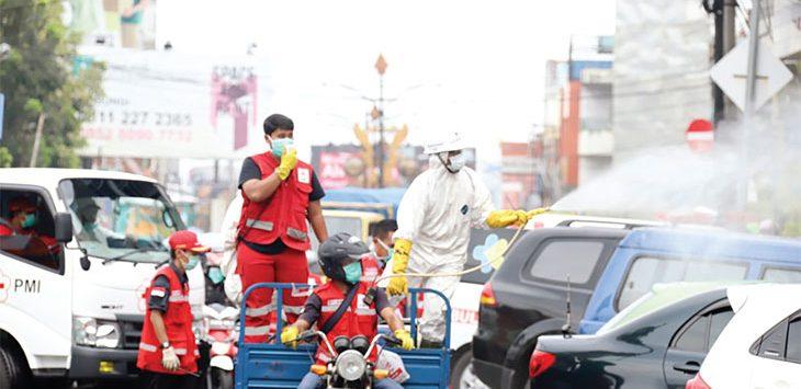 Sejumlah petugas gabungan saat menyemprotkan disinfektan di Jalan Ahmad Yani.