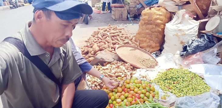 Seorang pedagang sayuran dan rempah-rempah di pasar Jalan Statiun Timur saat melayani pembeli, rabu (25/3).