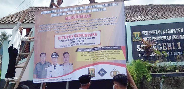 Anggota Polsek Cidahu saat memasang baliho himbauan penutupan sementara destinasi wisata, rabu (1/4/2020).