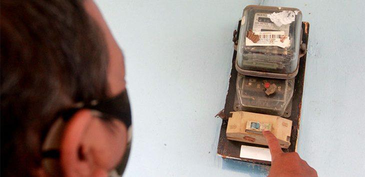 Warga menunjukkan meteran listrik yang berada di rumahnya. Ist