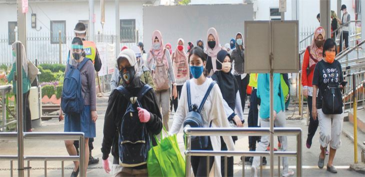 Sejumlah penumpang KRL Commuter Line menggunakan masker dan pelindung wajah saat keluar Stasiun Depok Lama, Kecamatan Pancoranmas.