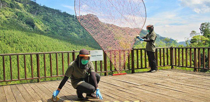 Petugas memasang garis pembatas jarak di Kawasan Wisata The Lodge, Lembang, Kabupaten Bandung Barat, belum lama ini.