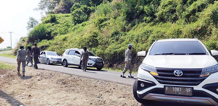 Sejumlah petugas Satpol PP Kabupaten Sukabumi saat melakukan cek poin di jalur objek wisata Geopark Ciletuh. Beberapa kendaraan terpaksa diputar balik karena masih nekat berkunjung ke tempat wisata ditengah pandemi Covid-19.