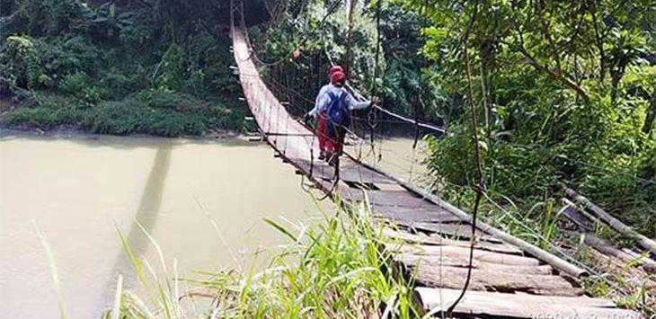 Warga saat melintasi jembatan Gunung Batu yang kondisinya rusak parah.