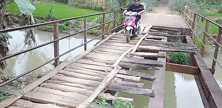 Seorang pengendara sepeda motor tampak hati-hati saat melintasi jembatan rusak.