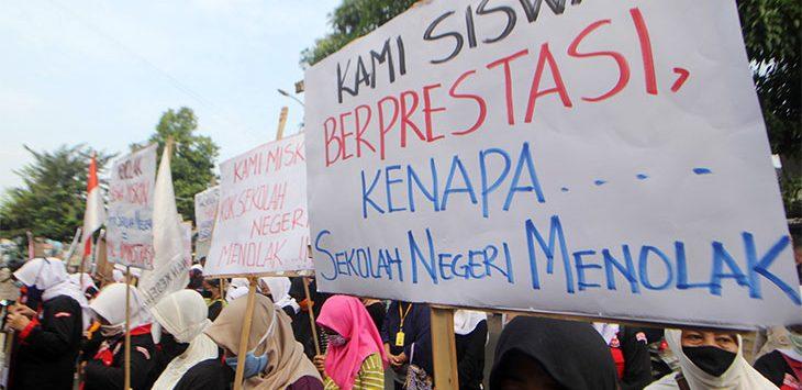 Sejumlah anggota Dewan Kesehatan Rakyat (DKR) bersama orang tua murid melakukan demo sebagai bentuk protes penolakan siswa miskin dalam Penerimaan Peserta Didik Baru (PPDB) di depan SMA Negeri 1, Jalan Nusantara Raya, Kecamatan Pancoranmas, Senin (13/7/2020).