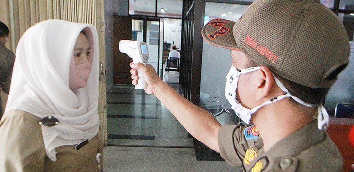 Petugas Satpol PP melakukan pemeriksaaan suhu tubuh kepada Aparatur Sipil Negara (ASN) di Gedung Baleka 2, Balaikota Depok guna penerapan protokol kesehatan.
