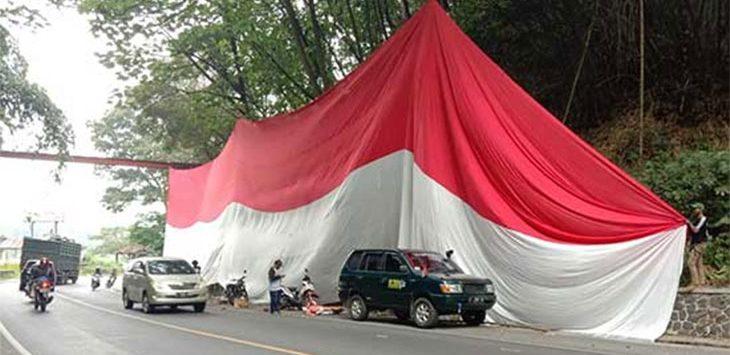 Bendera merah putih raksasa panjang 35 meter dan lebar 8 meter yang terbentang di Jalan Nasional tepatnya di Bojongkokosan, Parungkuda, Kabupaten Sukabumi, Kamis (13/8/2020).