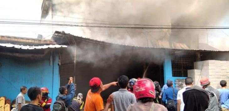 Pemadam kebakaran dibantu warga masyarakat sekitar saat bahu membahu menjinakan sijago mereh di toko bangunan ADE di wilayah Pondoksalam.