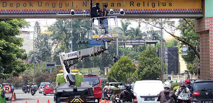 Petugas sedang memasang kamera pemantau sistem tilang elektonik atau Electronic Traffic Law Enforcement (ETLE) di kawasan Jalan Margonda Raya, Kamis (17/9).