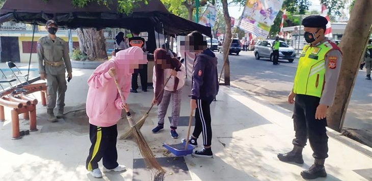 Petugas gabungan saat memberikan sanksi sosial kepada warga dan wisatawan yang kedapatan melanggar protokol kesehatan salah satunya tak memakai masker untuk menyapu badan trotoar di seputaran Alunalun Palabuhanratu, Minggu (20/9).