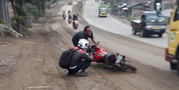 Tampak seorang warga tengah membangunkan motor yang terpeleset dan terguling akibat jalan yang licin bercampur tanah dan lumpur di jalan utama Bandung-Purwakarta, tepatnya di Dekat perempatan Cilalawi tempat keluar masuknya kendaraan besar pengangkut batu split.