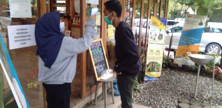 Pengunjung diperiksa protokol kesehatan sebelum masuk kafe. Arif