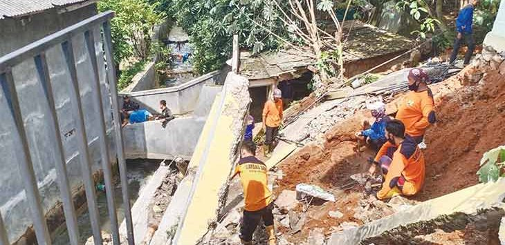 Para petugas dari Dinas PUPR bersama petugas lainnya saat berusaha merapikan material longsor yang terjadi di RT02/03, Kelurahan Sukamaju, Kecamatan Cilodong, agar aliran sungai tidak tertutup material longsor, Selasa (9/2).