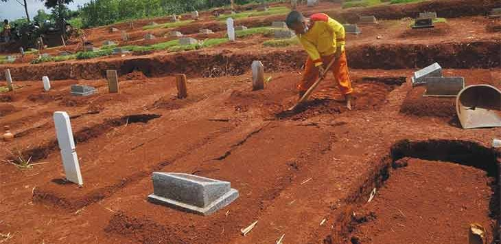 Koordinator TPU Karabha Tapos, Tajudin saat memperbaiki salah satu makam yang amblas akibat hujan deras yang menghujam Kota Depok, sekitar ada 11 makam yang mengalami amblas dan sedang dalam perbaikan, Kamis (4/2/2021).