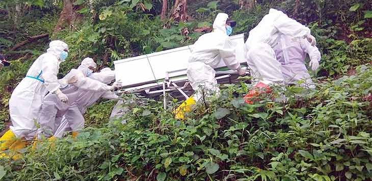 Petugas kesehatan dari Satuan Tugas (Satgas) Covid-19 Kabupaten Sukabumi saat melewati medan yang cukup sulit ketika akan memakamkan pasien Covid-19 yang meninggal dunia di pemakaman.