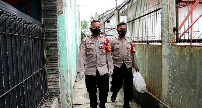 Polsek Dayeuhkolot bagikan sembako ke warga yang sedang isolasi mandiri. Foto/Arif