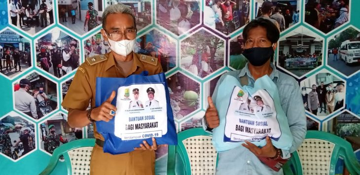 Lurah Nagasari, Ade Sukardi menyerahkan bantuan untuk warga Isoman. (ega/pojokjabar)