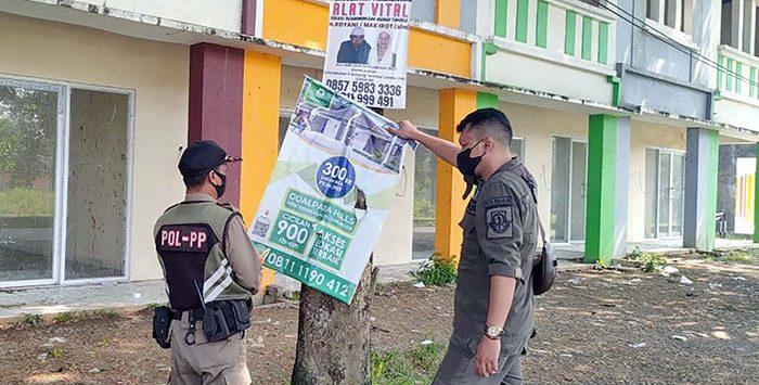 Sejumlah petugas Satpol PP Kota Sukabumi saat melakukan penertiban baloho yang menempel di pohon